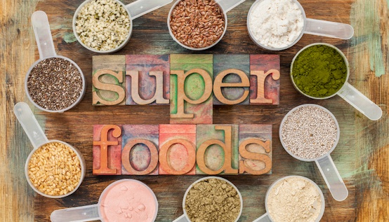 superfoods word in letterpress wood type surrounded by plastic scoops of healthy seeds and powders (chia, flax, hemp, pomegranate fruit powder, wheatgrass,  whey protein, maca root) - top view